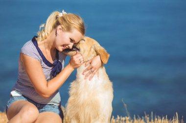 Young woman, labrador dog, sea
