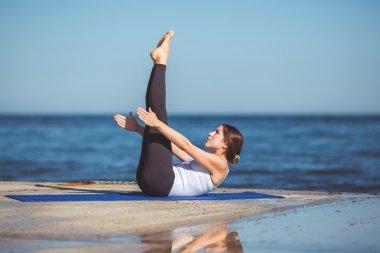 Young woman, sea shore, yoga exercises