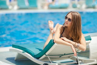 Woman sunbathing in bikini at tropical travel resort. Beautiful young woman lying on sun lounger near pool