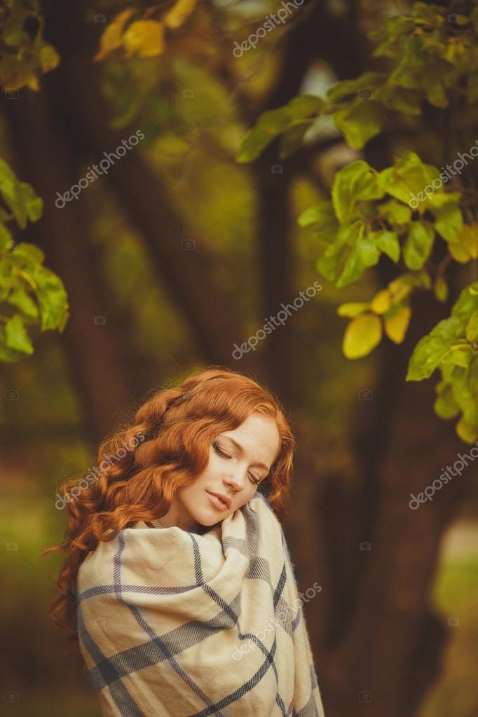 Portrait of young beautiful redhair woman standing in green summer park