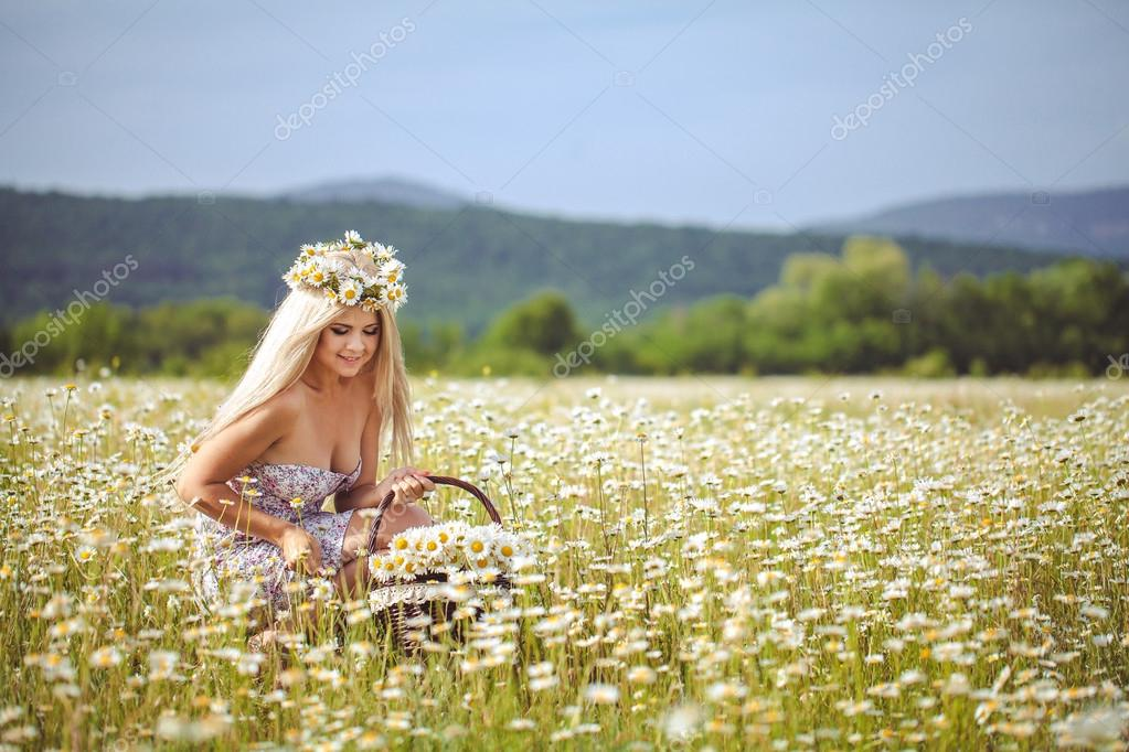 Attractive blonde in chamomile field. Young woman in wreath