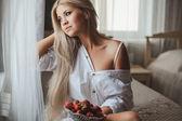 Fotografie Junge Frau mit auf Bett mit Erdbeere