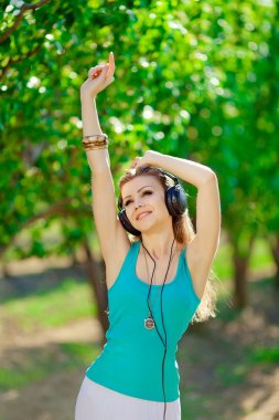 Beautiful young woman listen to music wearing headphones outdoor