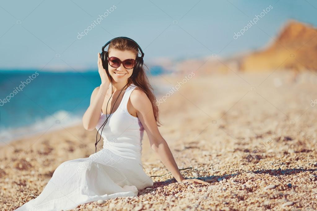 Beautiful woman listening to music against blue sky in headphones on the seashore