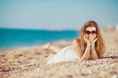 Portrait of a beautiful young woman on the beach in the sand