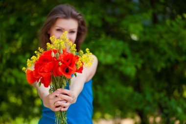 Portrait of cheerful woman outdoor with red poppy flowers in her hands