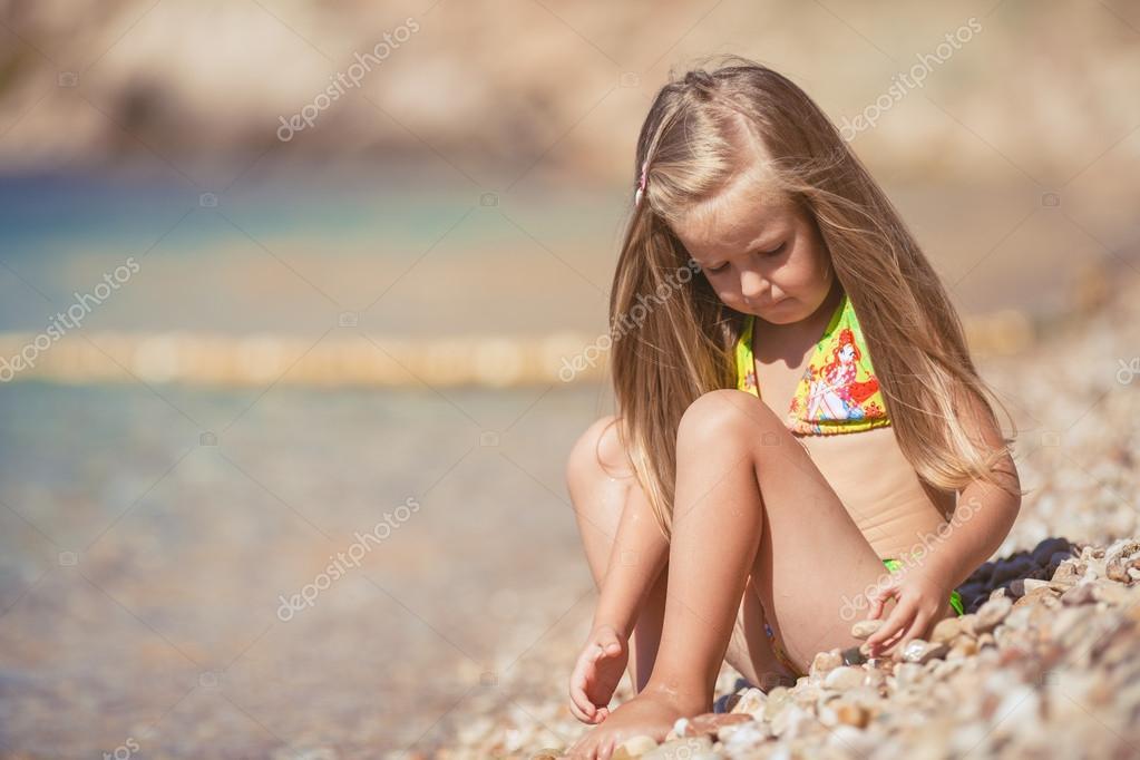Little girl sitting on the beach near the sea