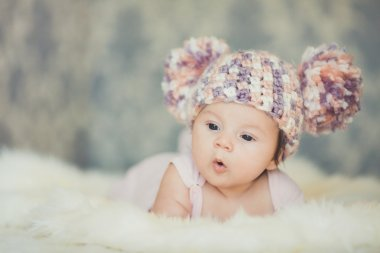 Cute newborn baby girl in knitted cap with bubonic