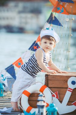 Cute little boy sitting on the floor on pier outdoor, a marine style. Little sailor