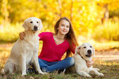 Portrait of Young girl sitting on the ground with her dog retriever in autumn scene