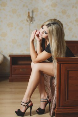 Portrait of sexy young blonde woman in lingerie sitting on the floor near the bed
