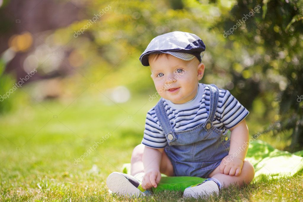Portrait of cute little boy sitting on the grass