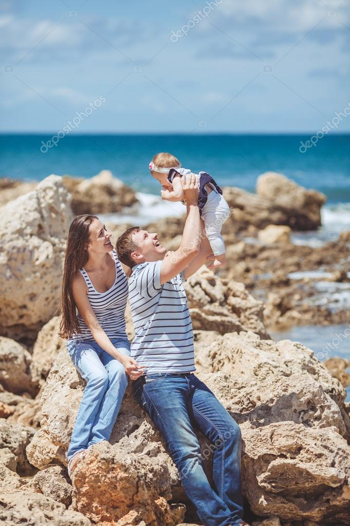 Portrait of family of three having fun together by the ocean shore and enjoying the view. Outdoors