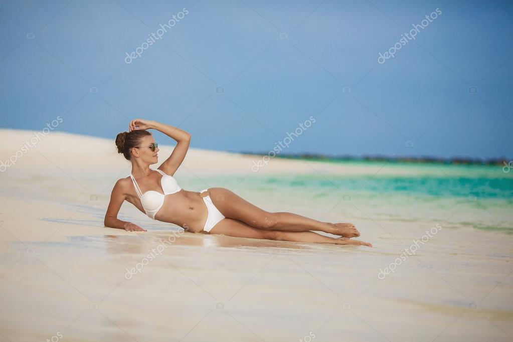 Portrait of Young beautiful women on the sunny tropical maldivian beach in bikini lying on the shore