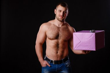 Image of muscular man holding xmas gifts, isolated on black