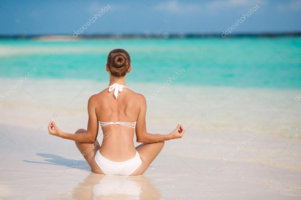 Portrait of young woman doing yoga exercises on tropical maldivian beach near ocean