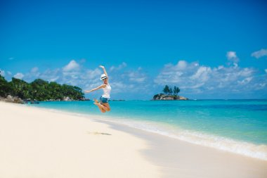 Summer and holiday concept - laughing woman jumping on the beach