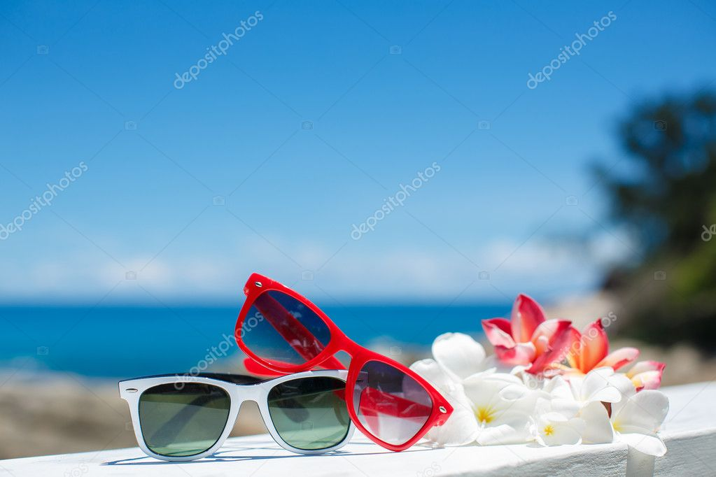 Two pairs of sunglasses on background of ocean