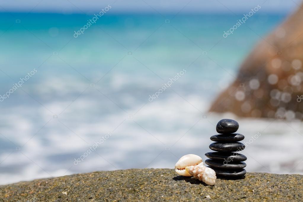 Zen stones jy on the sandy beach near the sea.