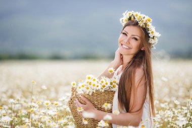 Beautiful girl on the camomile field