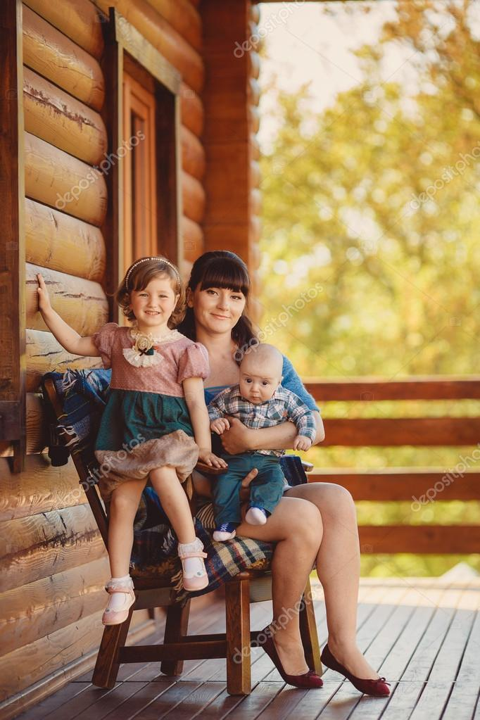 MOM with kids, sitting near a wooden house