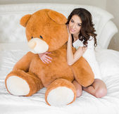 Photo Pretty girl lying on the bed with a teddy bear
