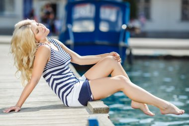 Adorable blonde woman wearing sea shorts and sexy sailor T-shirt sitting on yachts background and the sea