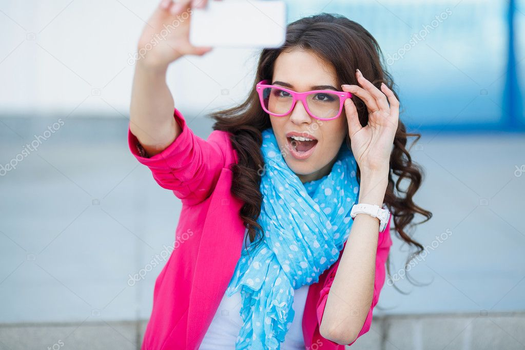 Happy young girl making funny face while taking pictures of herself through cellphone, over white background