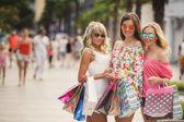 drei Mädchen mit Einkaufstaschen und gehen einkaufen.
