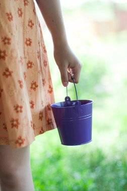 Child hands with a bucket in it