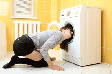 Ordinary simple beautiful girl put her head into a washing machine