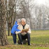Fotografie Großvater und Enkel, die Lektüre eines Buches im freien
