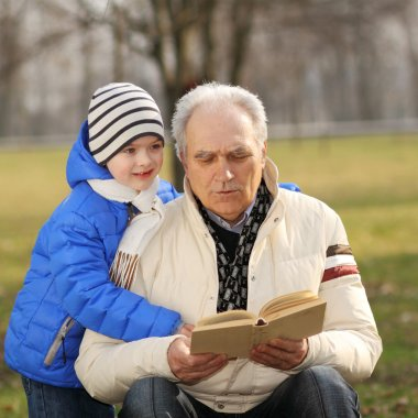 Grandfather and grandson reading a book outdoors