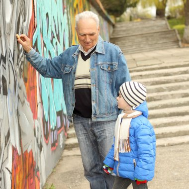 Grandfather and grandson paint graffiti