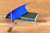 Graduation mortarboard on top of stack of books