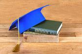 Fotografie Graduation mortarboard on top of stack of books
