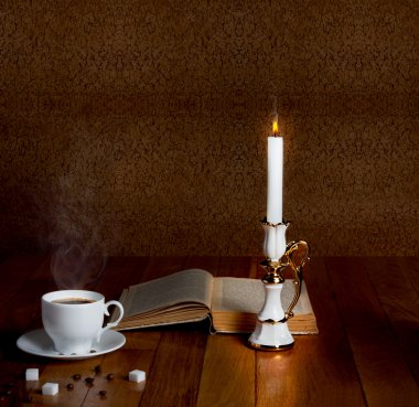 Hot cup of fresh coffee on the wooden table with  candle and book