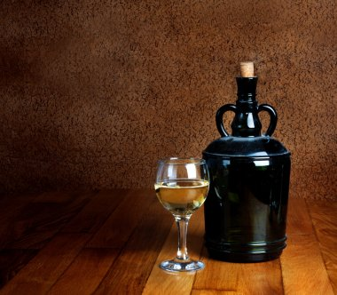 Dusty old bottle and glass of white wine on a wooden table