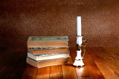 Old stack of books with candlestick