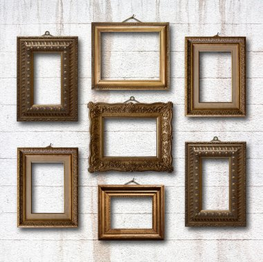 Gilded wooden frames on old stone wall