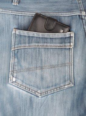 Black leather wallet sticking in the back pocket of denim  blue