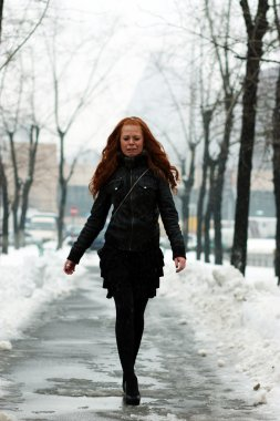 Young woman walking down snow covered street
