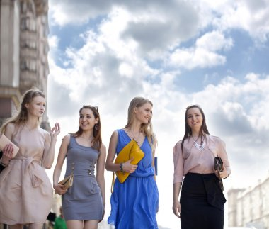 Four beautiful fashion girls walking on the street