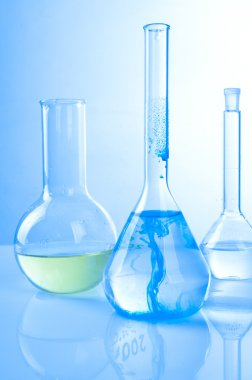 Glass laboratory equipment on blue background