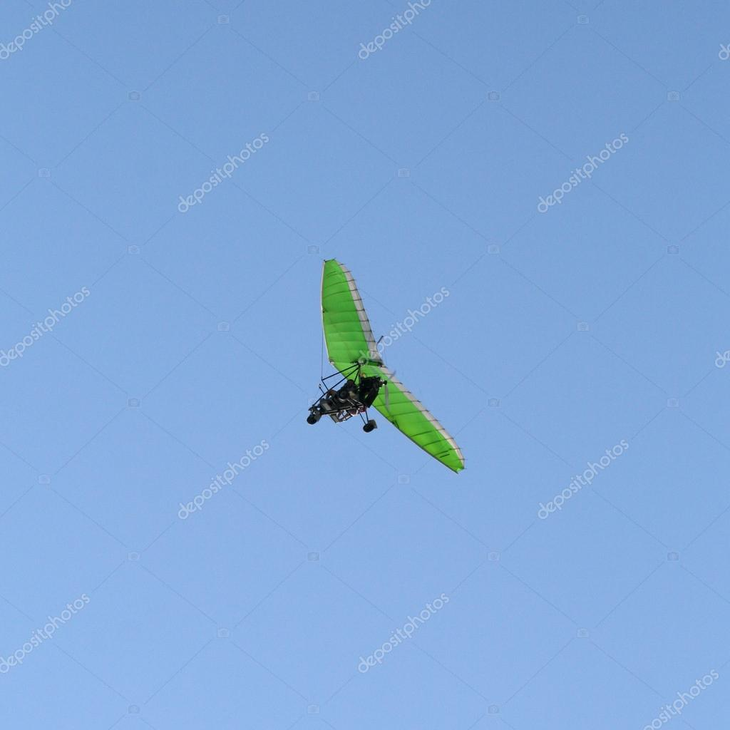 Green Motor hang glider in a clear blue sky