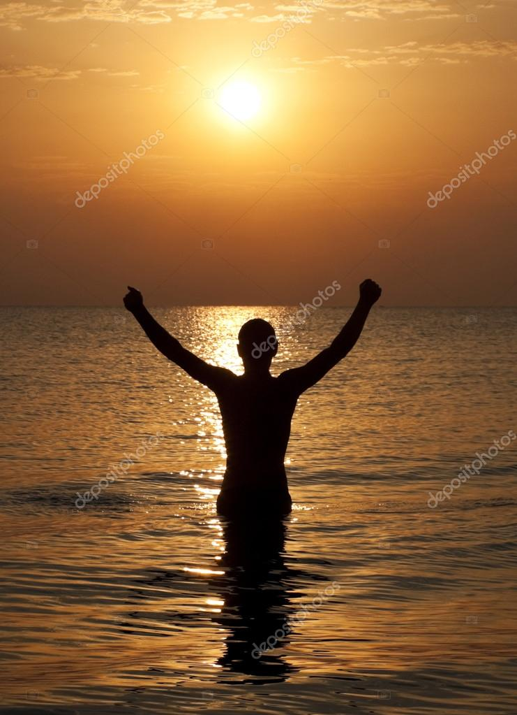Siluette of man in water on sunset
