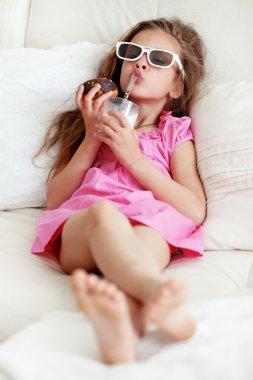 Kid girl eating on a sofa