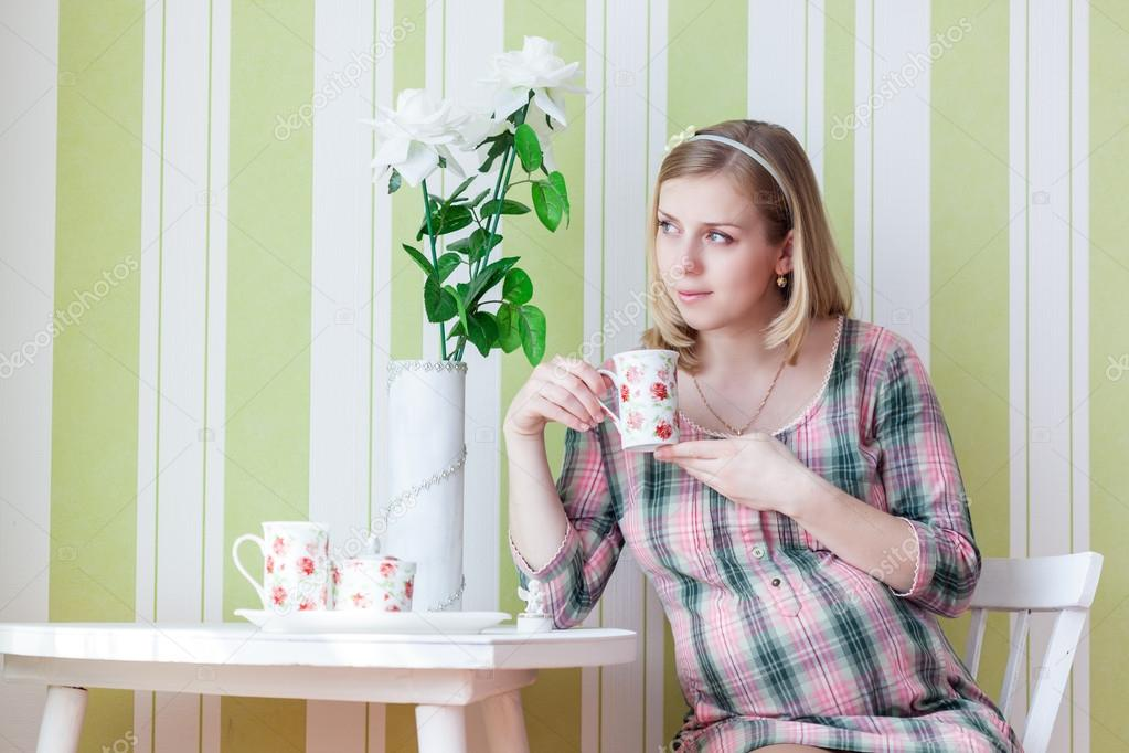 Pregnant woman is drinking tea