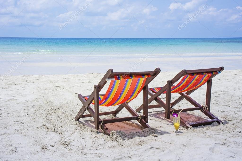 Two beach chairs on the white sand beach before blue sea on a beautiful tropical beach