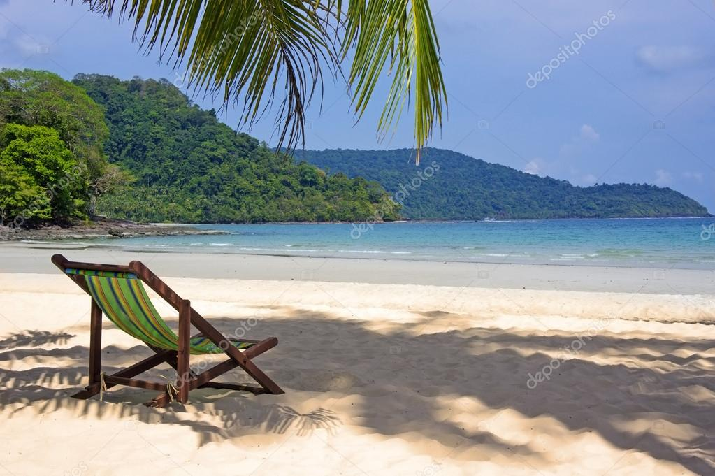 Tropical Beach. Beach Chairs On The White Sand Beach, Foreground With Palm  Leaf U2014